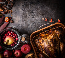 Thanksgiving Background. Whole Roasted Stuffed Turkey On Dark Rustic Table With Apples, Cranberries, Various Nuts, Chestnuts , Candles And Autumn Leaves Decoration, Top View