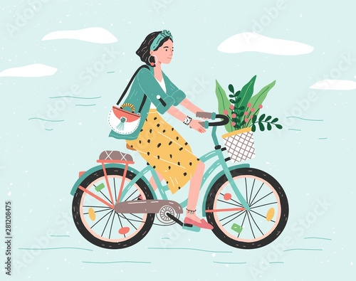 Tela  Happy girl dressed in trendy clothes riding city bicycle with flower bouquet in front basket