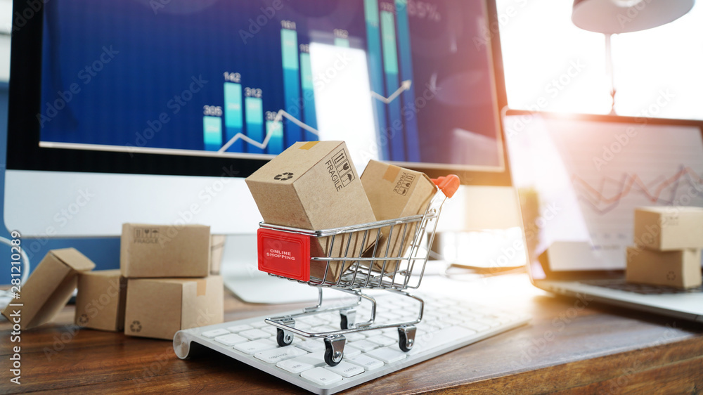 Fototapeta E-commerce. Paper boxes in shopping cart and credit card on keyboard and sales data economic growth graph on computer  screen, online shopping and payments, banking, services online on network.