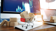 E-commerce. Paper Boxes In Shopping Cart And Credit Card On Keyboard And Sales Data Economic Growth Graph On Computer  Screen, Online Shopping And Payments, Banking, Services Online On Network.