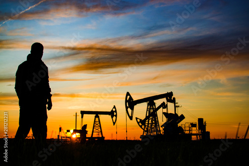Fototapeta Silhouette of the worker on the background of oil rockers. Sunset. Oil production in Russia. obraz