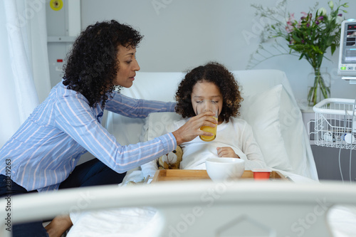 Mother feeding her son orange juice in bed in the ward