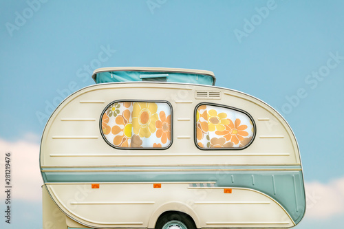 Fotografia Vintage seventies white caravan in front of a blue sky with clouds