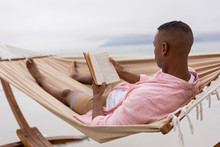 Man Reading A Book While Relaxing On A Hammock At Beach