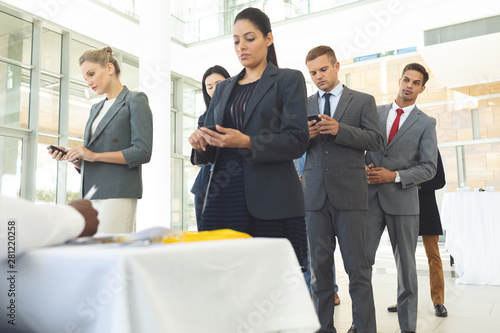 Group of diverse business people texting on mobile phone while queuing up for interview