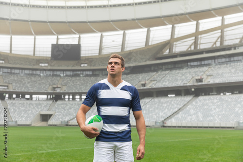 Caucasian rugby player standing with rugby ball in stadium