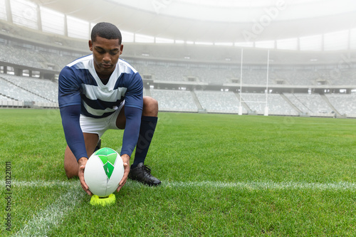 African American male rugby player placing rugby ball on the stand in stadium