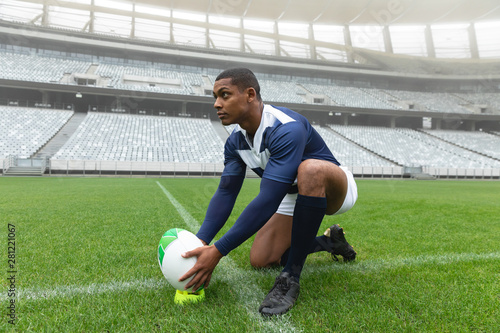 African American male rugby player placing rugby ball on a stand in stadium