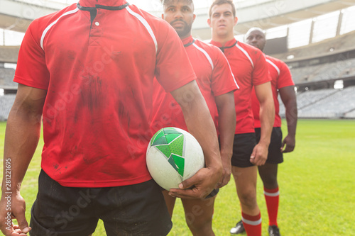Male rugby players standing together with rugby ball in stadium