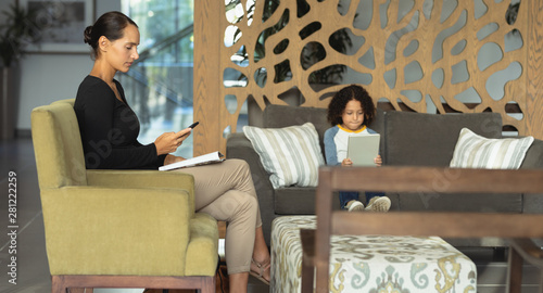 Mother and son using mobile phone and digital tablet in the lobby