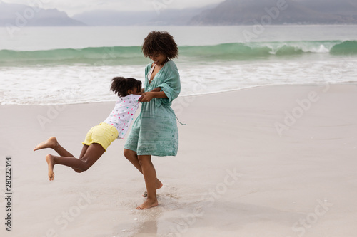 Mother and daughter having fun on the beach