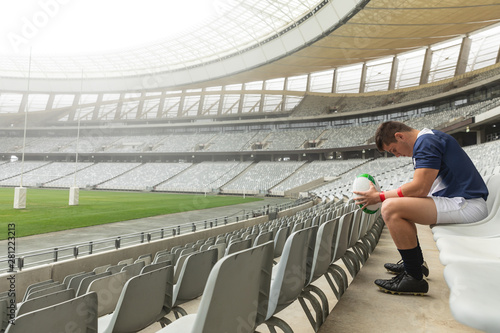 Upset Caucasian male rugby player sitting with rugby ball in stadium