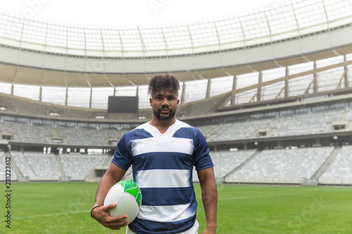 African American rugby player standing with rugby ball in stadium
