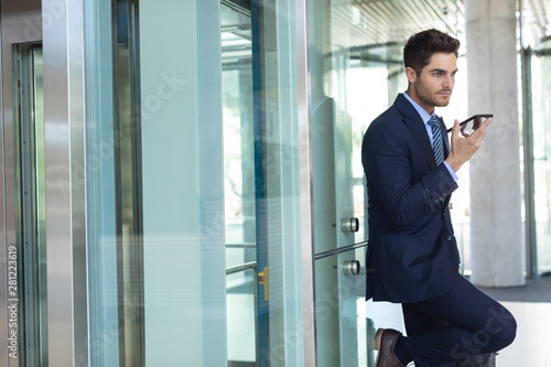 Young Caucasian businessman speaking on mobile phone while standing in modern office