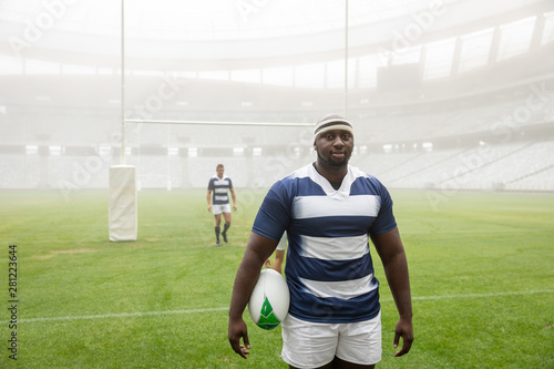 African american male rugby player holding a rugby ball in stadium