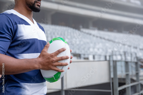 African American male rugby ball player holding a rugby ball in stadium