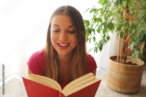 Young pretty woman sitting and reading a book enjoys of rest Canvas Print