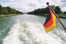 Boat Cruise On Mittellandkanal ( Midland Canal ) In Germany Between The Towns Of Minden And Bad Essen - Rear View With Backwash Wake And German Flag