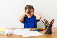 Little Boy Painting And Doing Homeworks On His Desk Covering Ears With Hands Trying Not To Hear Too Loud Sound.