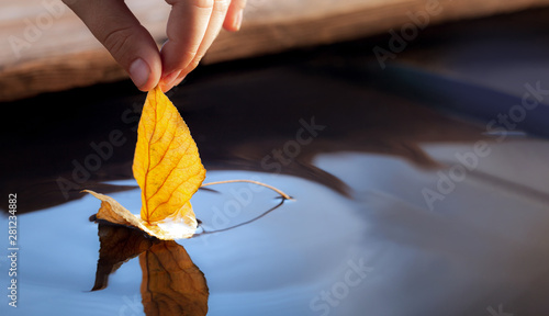 Canvas Prints Countryside yellow autumn leaf ship in children hand, boy play in water pond