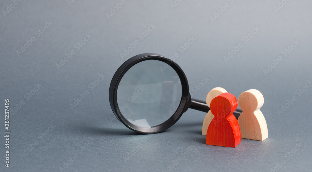 Fototapeta Three wooden human figure stands near a magnifying glass on a gray background. The concept of the search for people and workers. Search for vacancies and work. Human resources, management.