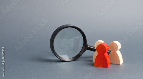 Three wooden human figure stands near a magnifying glass on a gray background. The concept of the search for people and workers. Search for vacancies and work. Human resources, management.