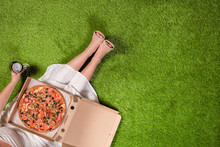 Picnic In The Garden On The Grass. Aerial View On A Young Woman In A White Summer Dress With A Pizza In A Box And A Glass Of Wine