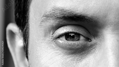 Fototapety, obrazy: Detail of an eye of a handsome man looking at camera. Details of a male face, closeup. Black and white photo