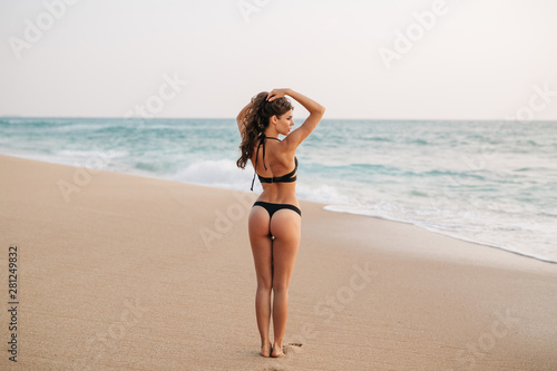 Slim brunette young girl in black swimsuit posing on the beach. Beautiful  woman with long hair relaxing at the ocean. Concept of sporty model, swimwear