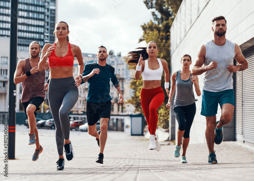 Fotografie, Obraz  Full length of people in sports clothing jogging while exercising on the sidewal