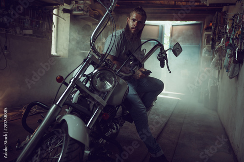 Handsome brutal man with a beard sitting on a motorcycle in his garage, wiping h Tablou Canvas