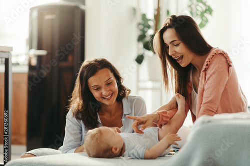 Two happy women having fun with their baby at home. Canvas Print