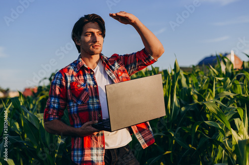 Portrait of young man agronomist standing in a  field with laptop and looking fa Canvas Print
