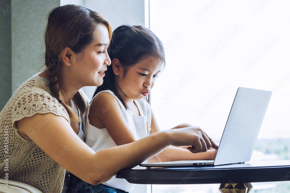Fototapety, obrazy: Mother and daughter using laptop together