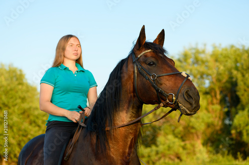 Photo The young horsewoman is sitting astride the thoroughbred horse.