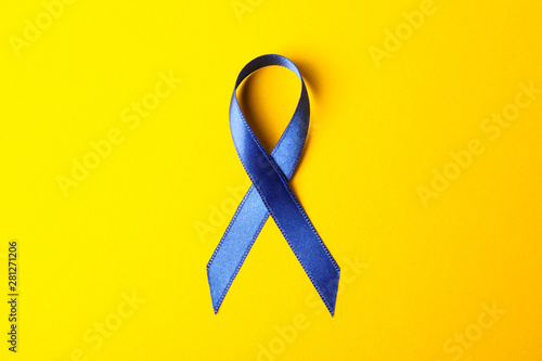 Vászonkép  Blue awareness ribbon on yellow background, space for text