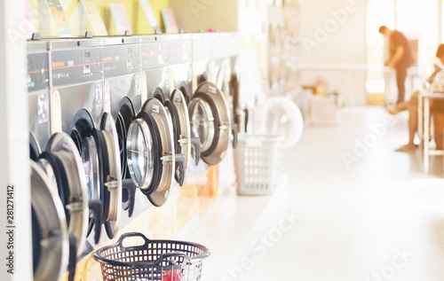 Fotomural Row of industrial laundry machines in laundromat  in a public laundromat, with laundry in a basket ,
