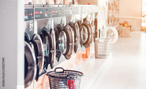 Valokuvatapetti Row of industrial laundry machines in laundromat  in a public laundromat, with laundry in a basket ,