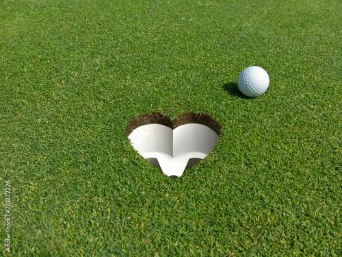 Fotografie, Obraz Ein Herz für Golf Golfloch in Herzform mit Golfball auf dem Puttinggrün