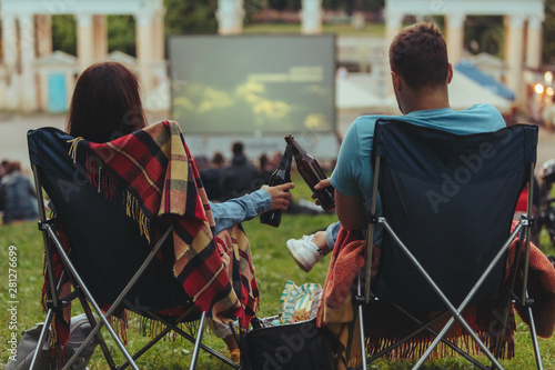 Fototapeta couple sitting in camp-chairs in city park looking movie outdoors at open air cinema obraz