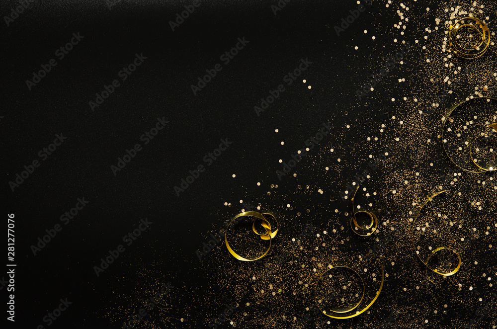 Fototapeta Golden sparkles and ribbons on black background. Festive concept. - Image