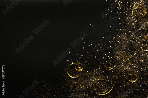 Fotografía  Golden sparkles and ribbons on black background