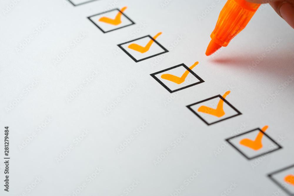 Fototapeta Orange marking on checklist box with pen, Checklist concept