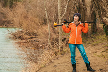 Search With A Metal Detector. A Young Woman Posing With A Metal Detector On The River Bank