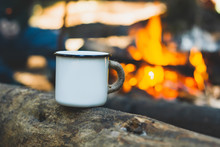 White Enamel Cup Of Hot Beverage Sitting On An Old Log By An Outdoor Campfire With A Vintage Folk Edit. Selective Focus On Mug With Blurred Background.