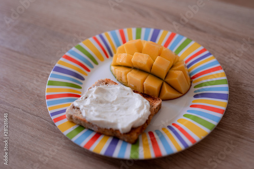 Cheese spread toasts with mango cut in cubes on a colorful plate on a wooden tab Wallpaper Mural