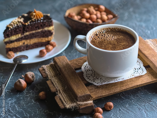 Foto auf Gartenposter Schokolade Breakfast. Coffee morning , with a slice of cake and hazelnuts on a textural background.