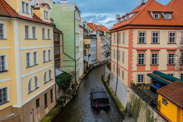 Fototapeta na wymiar water channel with river of Certovka (Devil's Channel) and boat, also called Little Prague Venice, in district of Lesser Town (Mala Strana) Prague, Czech Republic, Europe