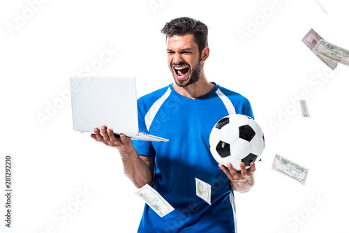 Fotomural cheering soccer player with ball and laptop near falling money Isolated On White