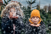 Siblings Playing With Snow Outdoors